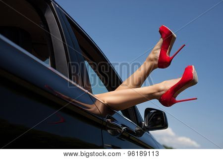 Sexy young woman feels freedom in her car