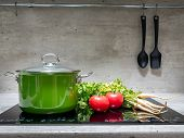 Green enamel stewpot with parsley and two tomatoes on black induction cooker poster