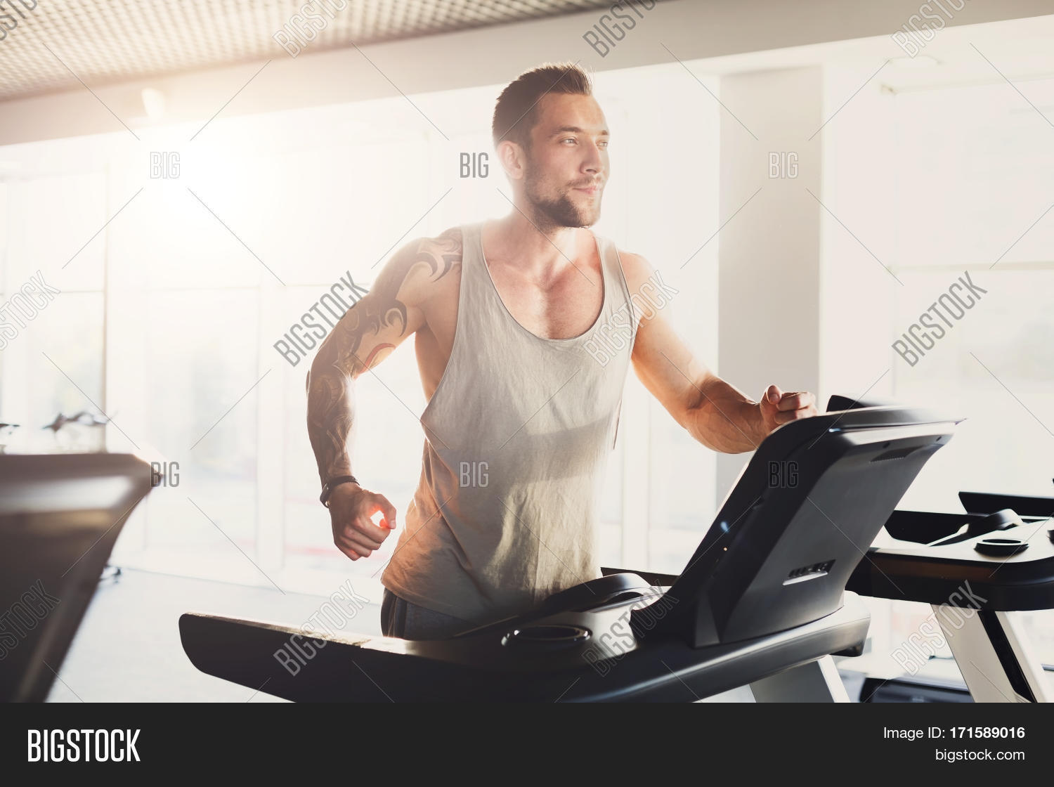 Young Happy Handsome Man With Tattoo In Fitness Club Cardio Workout Running On Treadmill