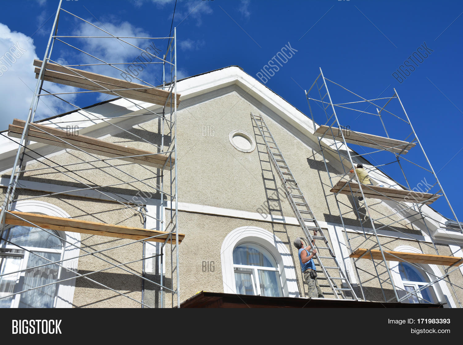 Painting And Plastering Exterior House Scaffolding Wall. Home Facade  Insulation And Painting Works During Exterior