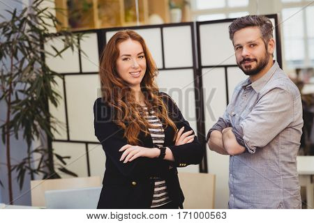 Portrait of confident creative business people with arms crossed standing in creative office