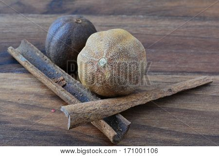 Pair of nutmegs and cinnamon sticks on dark wooden chopping board