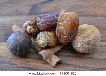 Small heap of date palm fruits a pair of cinnamon sticks and nutmegs on a dark wooden chopping board close up view