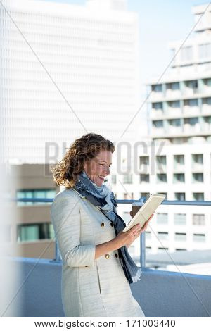 Mature woman using digital tablet by railing in city