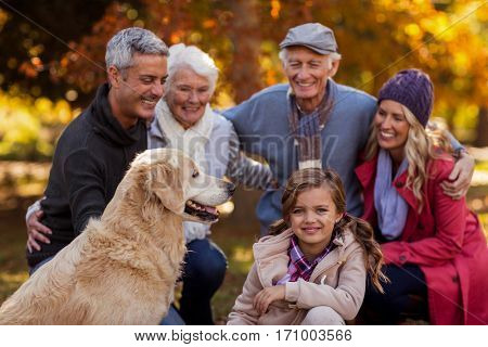 Cheerful multi-generation family with dog at park during autumn