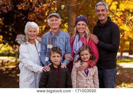 Portrait of multi-generation family standing at park during autumn