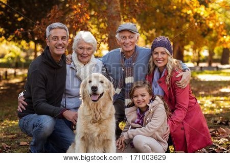 Portrait of multi-generation family with dog at park during autumn