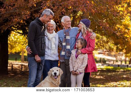 Multi-generation family standing with dog at park during autumn
