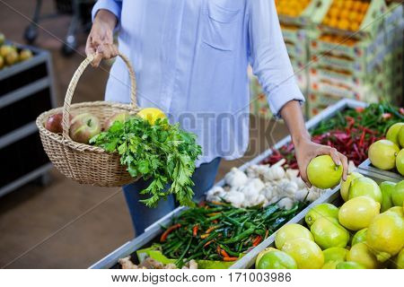 Mid section of woman buying sweet lime in organic section of supermarket