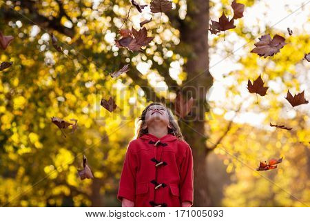 Happy girl standing against tree with autumn fall at park