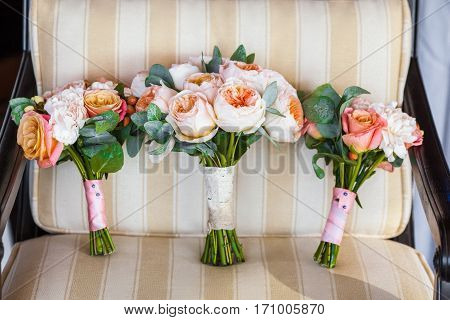 Beautiful wedding bouquet lies on vintage beige chair. Bouquet consists of peach and white roses. Close-up