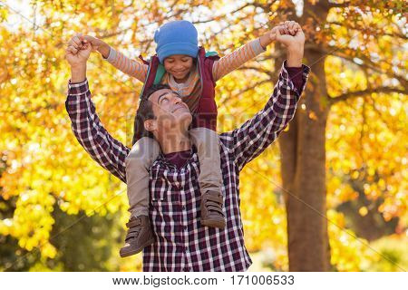 Happy father carrying son on shoulder at park during autumn