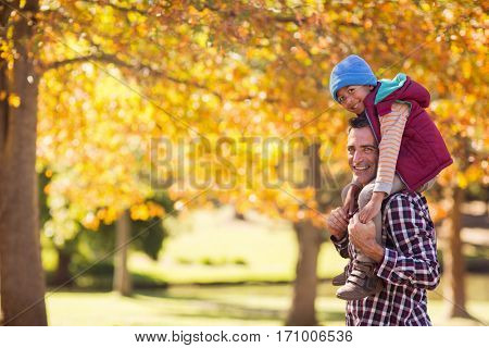 Portrait of father carrying son on shoulder against autumn trees at park