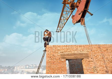 Athletic builder leaning on brick wall and sitting on ladder on high. Male with bare torso in work wear looking at distance away. Iron crane on background.