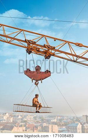 Side view of athletic man in hat sitting and resting on construction on high and eating. Large building crane holding construction with male over city in air. Cityscape and blue sky on background.