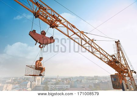View of muscular man in hat resting and sitting on construction on high and eating. Extreme building of house in big city. Building crane holding construction with male over city in air.
