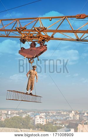 Builder with bare torso standing on iron construction on high and holding by ropes. Wearing hat and work wear looking away at distance. Extreme building. Blue sky on background.