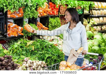 Woman buying carrot in organic section of supermarket