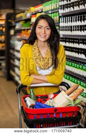Portrait of smiling woman standing with shopping cart in grocery section of supermarket