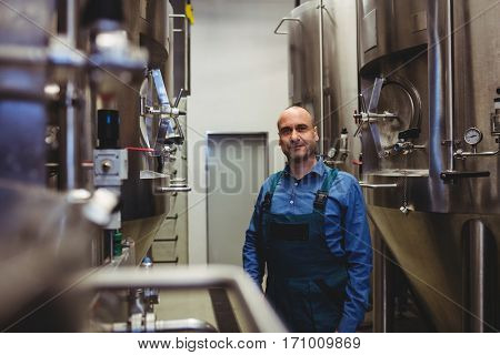 Portrait of confident owner standing amidst manufacturing equipment at brewwery