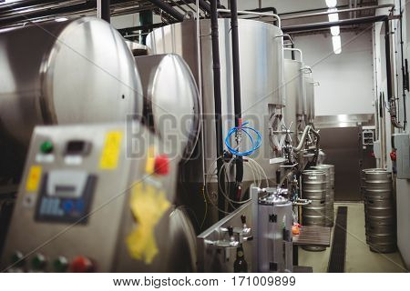 Machinery and kegs in illuminated brewery