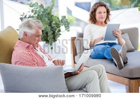 Mature couple using laptop and digital tablet on couch at home