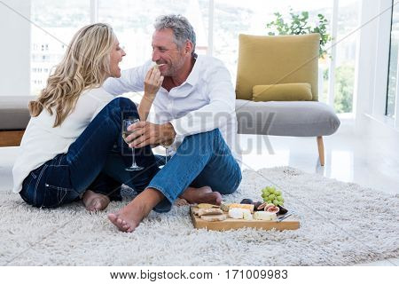 Happy woman feeding man while sitting on rug at home