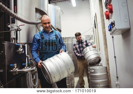 Worker and manufacturer carrying kegs at brweery