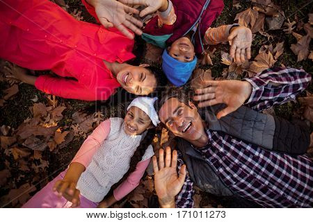 Overhead portrait of happy family gesturing while forming huddle on field