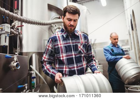 Manufacturer and worker lifting kegs at brewery