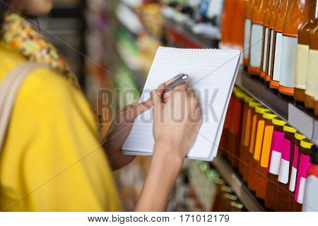 Woman at grocery section writing in notepad at supermarket