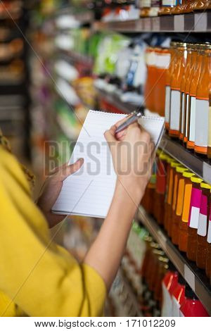 Mid section of woman at grocery section writing in notepad at supermarket
