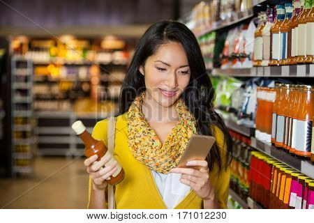 Woman using mobile phone while shopping for grocery in supermarket