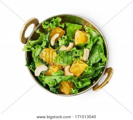 Vegan and vegetarian dish, fresh vegetable and fruit salad in copper bowl, top view isolated on white background. Indian restaurant healthy meal, lettuce, cashew and orange. Eastern local food.