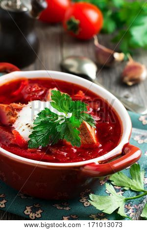 Beetroot soup with meat sour cream and parsley in a brown ceramic bowl on the old wooden background. Borsch- traditional dish of Ukrainian cuisine. Selective focus.