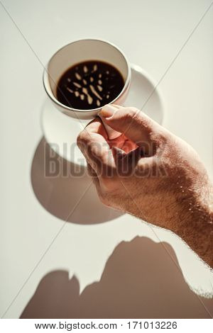 Close-up partial view of male hand holding white coffee cup