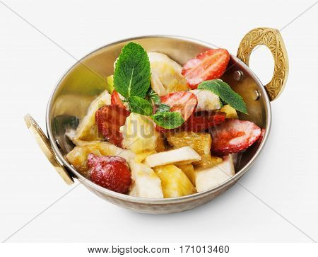Vegan and vegetarian dish, fresh fruit and strawberry salad in copper bowl closeup isolated on white background. Indian restaurant healthy meal, dessert. Eastern local food.