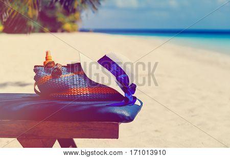 Beach vacation concept - bag, sun glasses and suncream at sea beach