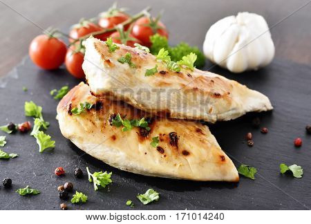 Grilled chicken breast on a slate plate with herbs and cherry tomatoes, garlic and peppercorns. Healthy eating scene, barbecue chicken.