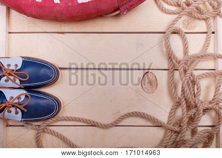 Blue boat shoes on wooden background near lifebuoy and rope. Top view. Copy space.