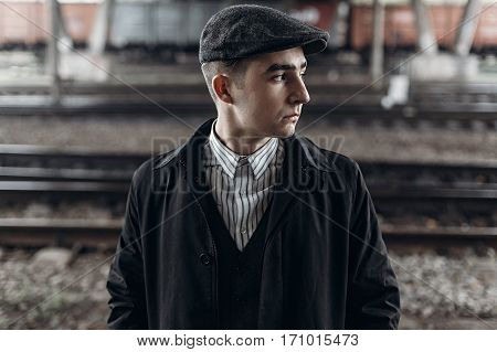 Stylish Man In Retro Outfit Posing On Background Of Railway. England In 1920S Theme. Fashionable Loo