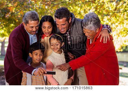 Happy multi-generation family taking selfie at park during autumn