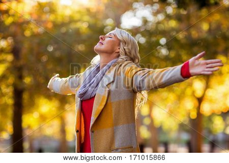 Young woman standing with arms outstretched against autumn trees at park