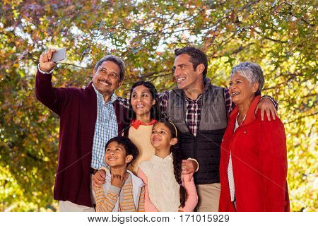 Cheerful multi-generation family taking selfie at park during autumn