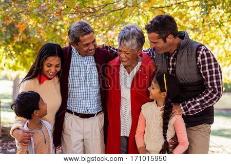 Cheerful multi-generation family standing at park during autumn