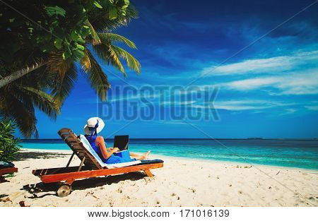 remote work concept -young woman with laptop on tropical beach