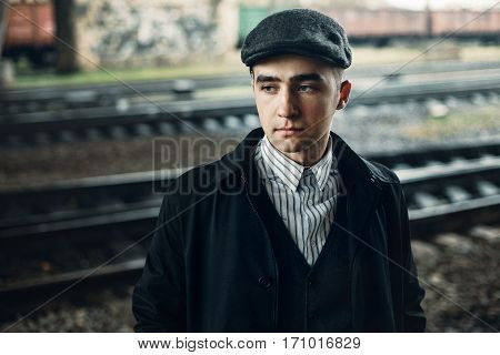 Stylish Men Portrait In Retro Clothes Posing On Background Of Railway. England In 1920S Theme. Old F