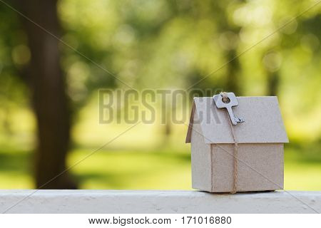 Model of cardboard house with key against natural green bokeh background. Building, housewarming, insurance, real estate or buying a new home concept. Outdoor.