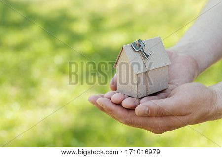 Male hands hold of cardboard house with key against natural green bokeh background. Building, housewarming, insurance, real estate or buying a new home concept. Outdoor.