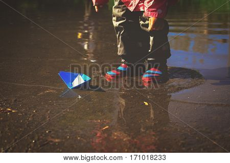 little girl playing with paper boats in water puddle